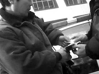 车管所内,中介老姚将一张身份证,一张驾驶证交予接头人。