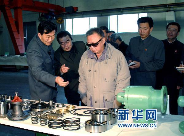 资料图:4月25日提供的照片显示,朝鲜最高领导人金正日(中)近日视察位于咸镜北道的龙城机械联合企业时观看产品。