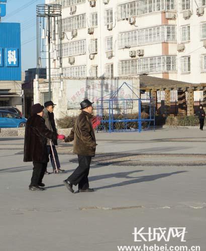 一对老人手牵手在广场上散步