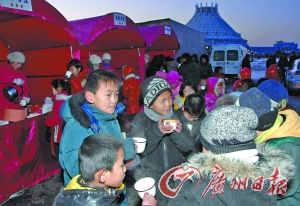 朝中社12月25日提供的照片显示,市民和少年儿童在吊唁场所现场设立的饮料摊位喝热茶驱寒。
