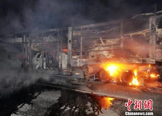大型拖车上的新车被大火烧毁。 柳坤 摄