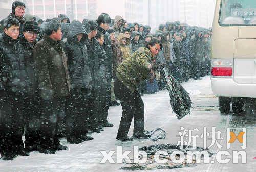 民众用衣物遮盖道路,防止车辆通过时打滑。 新华社发