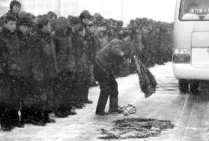 12月28日,在朝鲜首都平壤,民众用衣物遮盖道路,防止车辆通过时打滑。新华社发