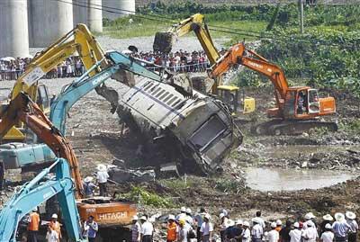 7月24日,几辆挖土机将损毁的车厢推向挖出的大坑