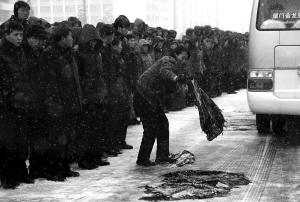 12月28日,在朝鲜首都平壤,民众用衣物遮盖道路,防止金正日灵车车队通过时打滑。