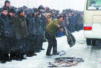 28日,朝鲜首都平壤,民众用衣物遮盖道路,防止金正日灵车通过时打滑。 新华社记者 张利摄