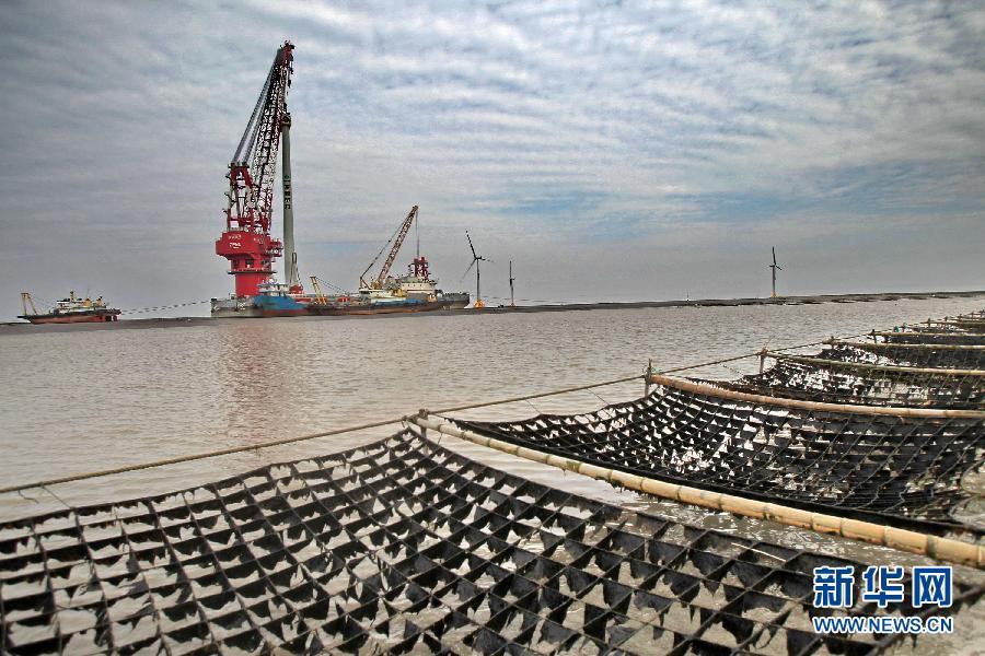 12月27日,国电龙源江苏如东海上风电场施工现场与一紫菜养殖场相映