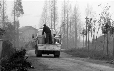 四川 孟祥超/12月28日,洪雅县阳坪村,一辆运奶车刚收走一名散户的鲜奶。...
