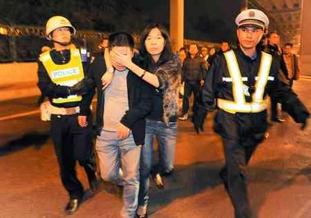 社会02-一名醉驾司机被交警截查时企图夺路狂奔,但当即被交警拦住,同车女子帮他挡住脸不给记者拍摄。 陆明杰 摄
