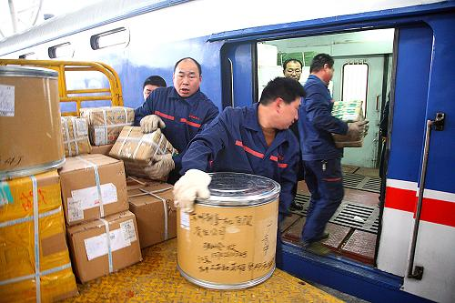 几名铁路装卸工人将包裹搬到一