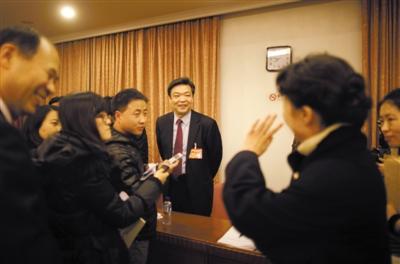 """昨晚,齐清代表仔细听取了常务副市长吉林关于经济问题的解答后,满意离去,她转身招手致意""""谢谢您""""。 本报记者 赵亢 摄"""