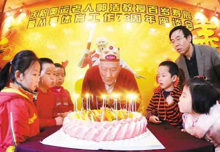 奥运老人郭洁教授与孩子们一起吹生日蜡烛。