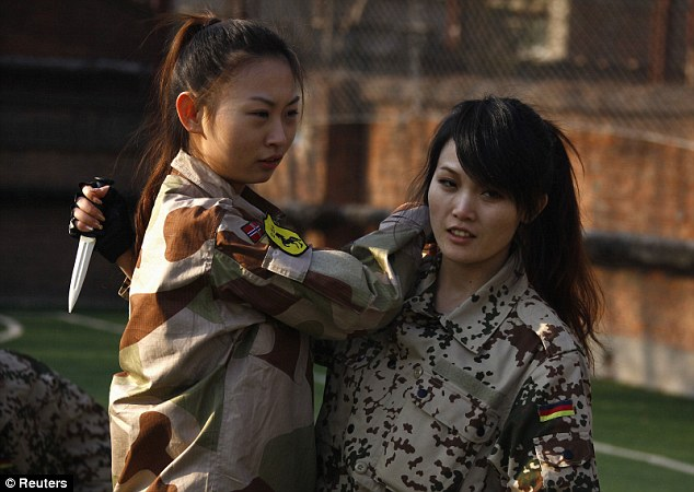 极端训练法:天骄特卫教官将啤酒瓶砸向一名女学员的头部。据悉,北京天骄特卫公司正在培训中国第一批女子私人保镖。