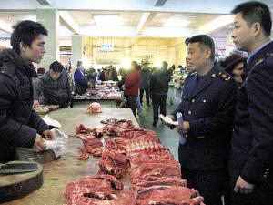 工商执法人员在市场检查平价猪肉销售情况。本报记者 雷倩倩摄