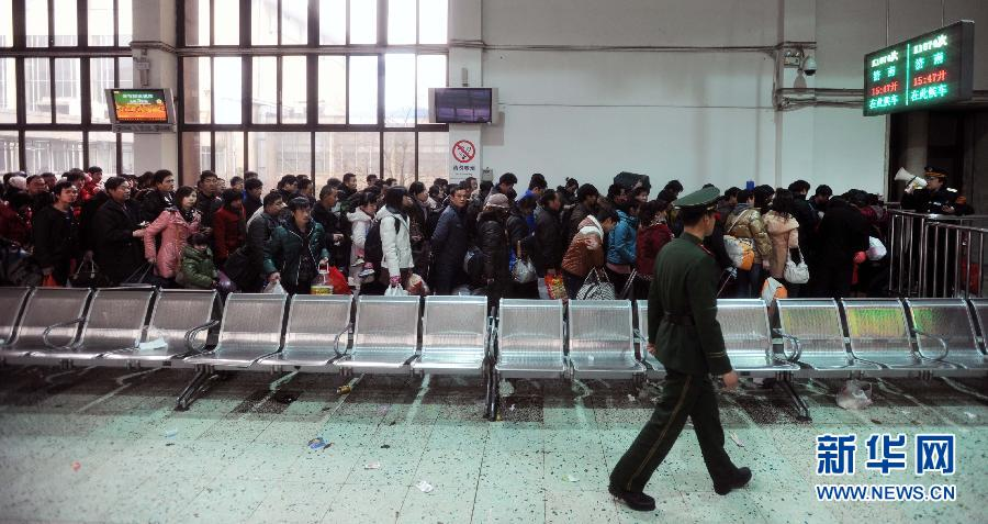 1月28日,在北京火车站广场西侧的地铁站前,刚抵达的旅客排队乘坐地铁.