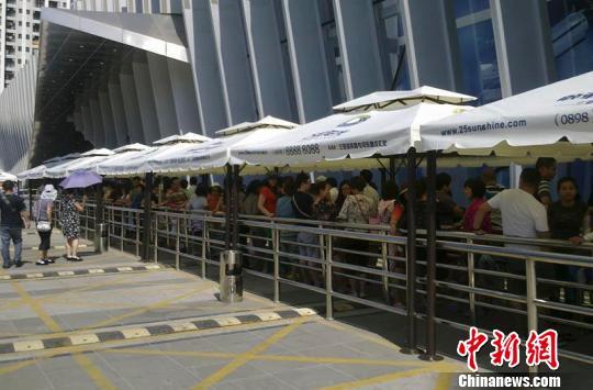 28日,游客排队等待进入三亚市内免税店购物。 尹海明 摄