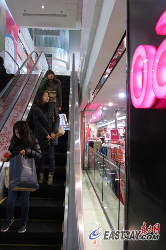 在巴黎春天百货长宁路店,扶梯外围都有十多厘米的隔板,隔板与楼板之间又隔开一段距离。