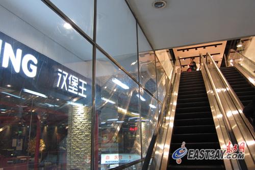 家乐福中山公园店B1层前的自动扶梯将扶手旁的空间用塑料隔板封死,乘坐扶梯的乘客无法探出头去。