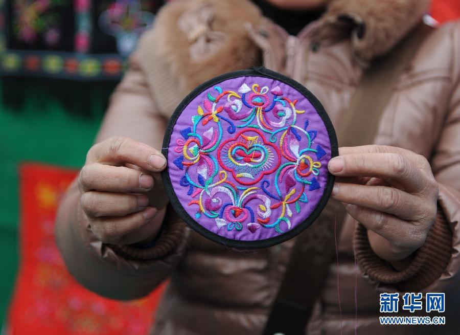 1月30日,一名仫佬族刺绣艺人向参观者介绍仫佬族刺绣 信袋