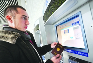 皮埃尔尝试用护照在自动售票机上买票。本报记者 张宁 摄