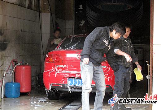 1月31日,沪浦东一汽修铺节后复工第二天,洗车工人们清洗家用轿车。