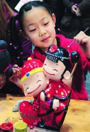 小女孩亲手绘彩陶