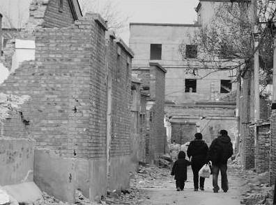 春节后,北京市昌平区的农民工领着孩子走在拆迁的村子中。 张志强摄