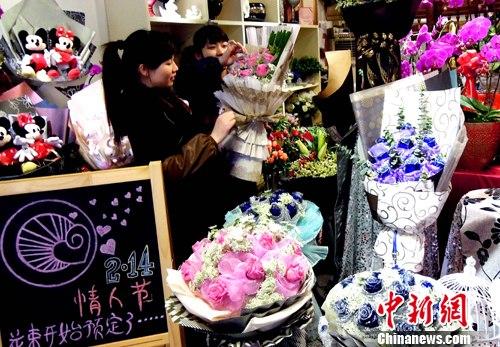 图为市区一花店员工正忙着包装今年情人节最流行的