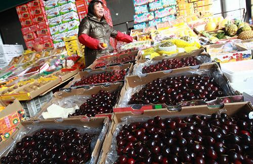 2月19日,上海农产品中心批发市场内,一位进口水果批发商在照看自己的摊位。新华社记者 裴鑫 摄