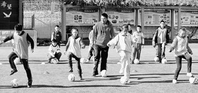 河北省秦皇岛市燕秀里小学学生在体育教师的指导下练习足球基本技术,享受足球运动的乐趣。