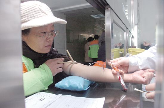 抽血自拍图片_医务人员正在为环卫工人抽血化验.
