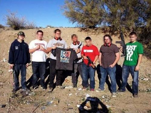 照片中的7个青年有的手持枪支,还有一人拿着一件印有奥巴马遭受枪击图像的T恤。