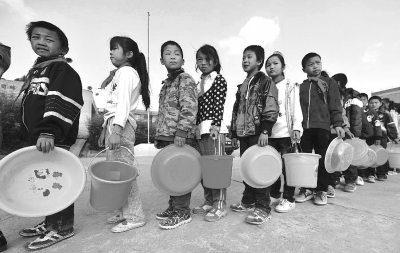 云南 罗贡/云南省陆良县小百户镇罗贡村小学的学生在排队等待取水。新华社...