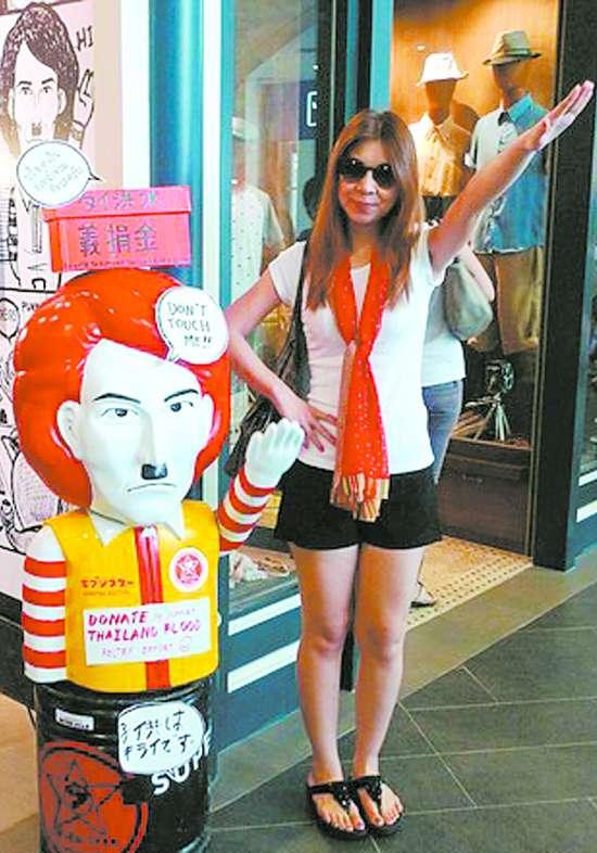 """少女 曼谷/曼谷一名少女站在""""希特勒""""的卡通人形立像旁,作出纳粹式的..."""