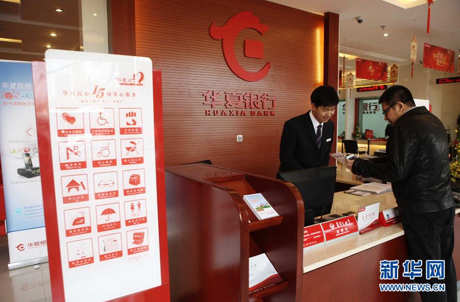 昆明/图为华夏银行昆明大观支行的大堂经理在为客户介绍业务。