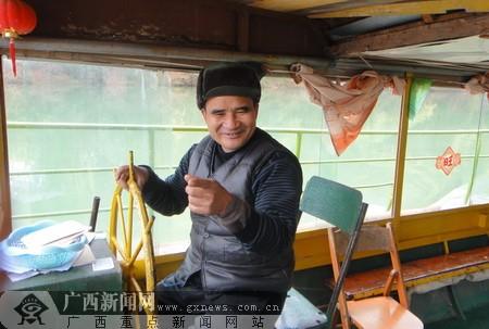 船长黄叔正在热情地向记者介绍花山情况。广西新闻网记者 邱璇 摄
