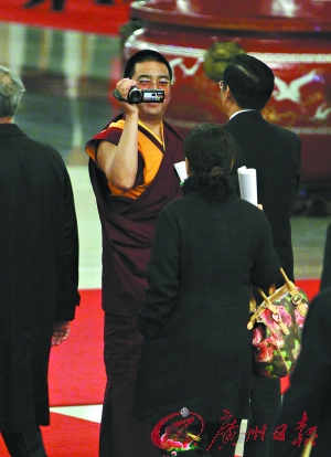 昨日,政协委员拉茂赛赤活佛一边入场一边跑前绕后拍DV。