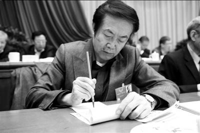 政协会议现场,袁熙坤用毛笔做笔记。中新社发