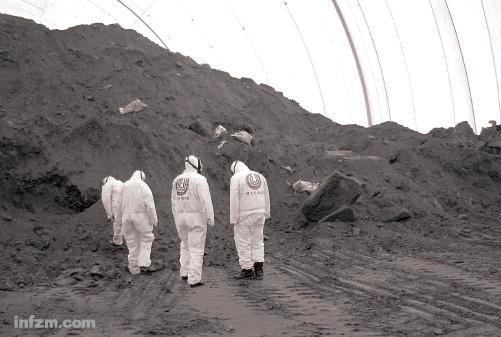 在贮存污染土壤的大棚内,身穿白色防护服、带着防毒面具的工作人员正在准备工作。 (中国环境修复资讯/图)