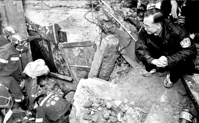 """2008年5月13日都江堰鼓励废墟中的小学生""""要挺住""""。新华社发"""