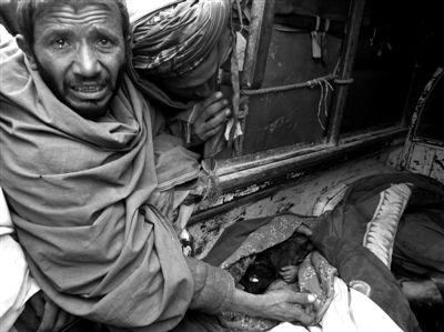 3月11日,一位阿富汗男子眼含热泪,旁边是被美军士兵射杀的平民尸体。