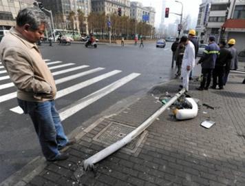 事发路口被公交车撞倒的路牌杆,一旁是公交车的反光镜