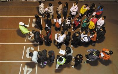 """昨日,清华大学体育馆,清华自主招生""""体质测试"""",工作人员引导学生们在场外排队等待测试。本报记者 薛�B影报道"""