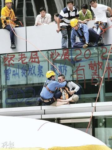 刘智仁(白衣盘腿坐者)当日在警察总部外墙喷字,情绪激动,经6个多小时扰攘后,刘方被制服。(资料图片)