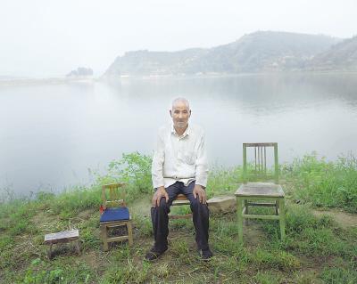 陕西省白水县林皋镇,66岁的焦栓成坐在家附近的湖边。焦栓成有3个孩子外出打工。