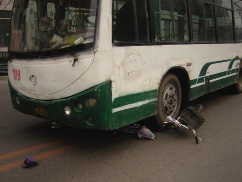 一辆公交车将一骑自行车女子撞飞,自行车被轧在车轮下.