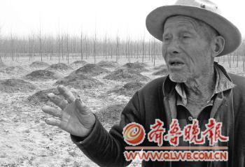 28日,户中宽老人为记者讲述当年那场战役,他身后就是烈士墓地。本报记者张歆然摄