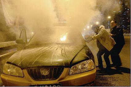 路过此地的几位好心司机,用自己的灭火器帮忙扑救 摄/记者郭谦