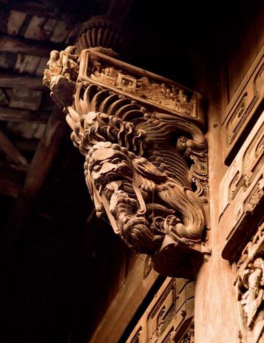 空旷高敞的龙门民居极为考究,厅堂的雀替、梁柱也是精致的木雕瓦兽,最有代表性的就是百狮厅,檐上的狮子木雕栩栩如生