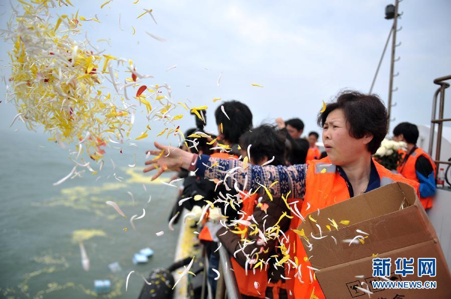 3月30日,一位参加海葬的逝者亲属将鲜花撒向大海.